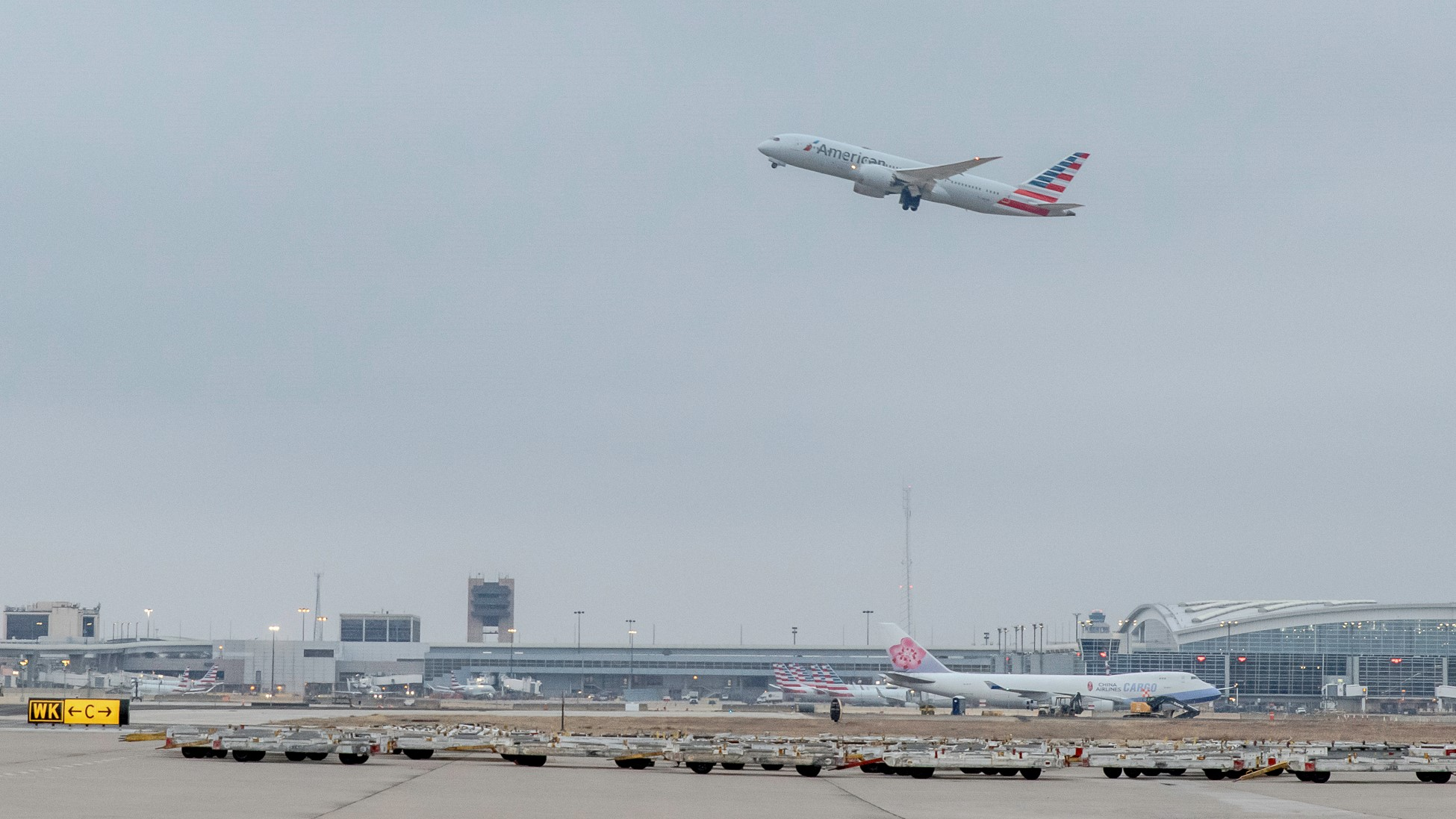 A plane rises above airport with cargo equipment in foreground.