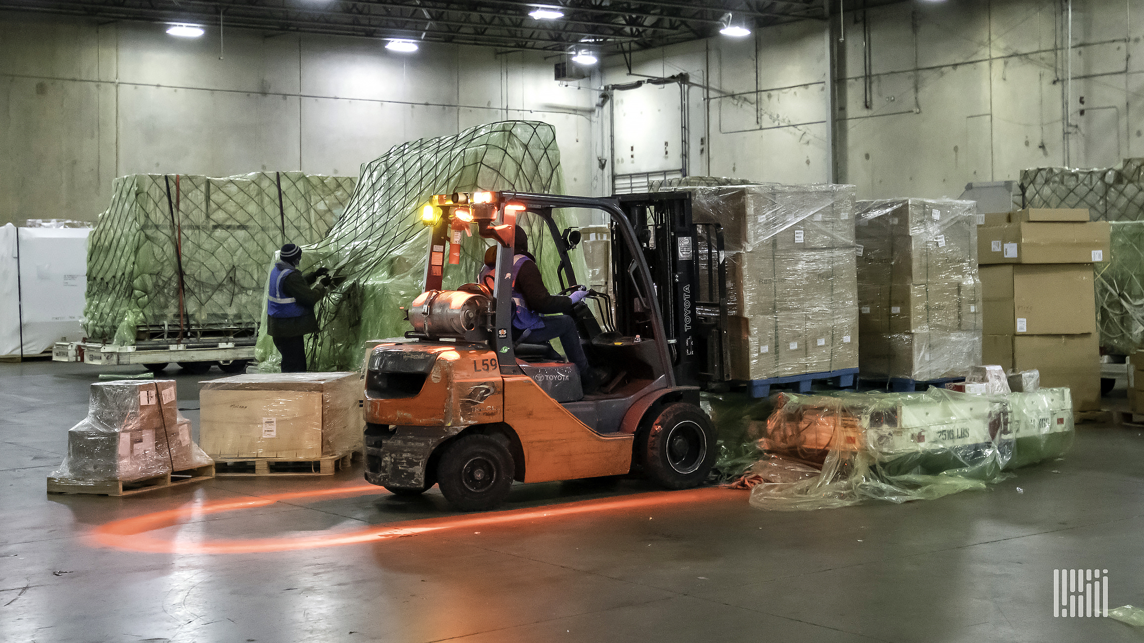 A forklift moving stacks of boxes in a warehouse.