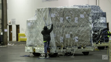 A worker secures cover over a large air cargo pallet.