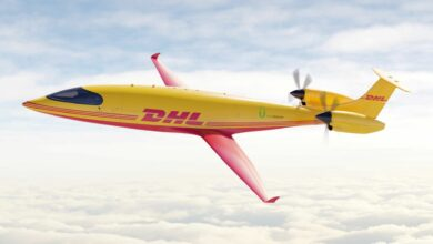 A rendering of a mustard-colored DHL electric cargo aircraft flying in the clouds.