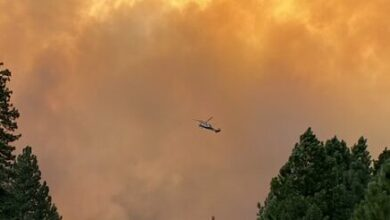 Helicopter dropping water onto the Dixie fire in northern California, Aug. 13, 2021.