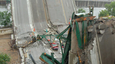 Cars are seen amidst the remains of the I-35W bridge on August 3, 2007. (Photo: NPR.org)