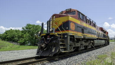 A photograph of a Kansas City Southern train turning around the curve.