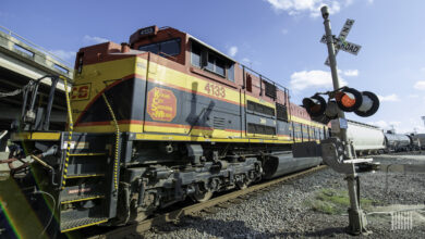 A photograph of a Kansas City Southern train rolling by a rail crossing.