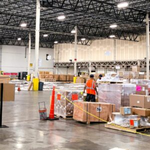 Boxes and loose cargo spread around warehouse floor.