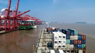A view from the back of a container vessel entering a port with tall cranes on the dock.