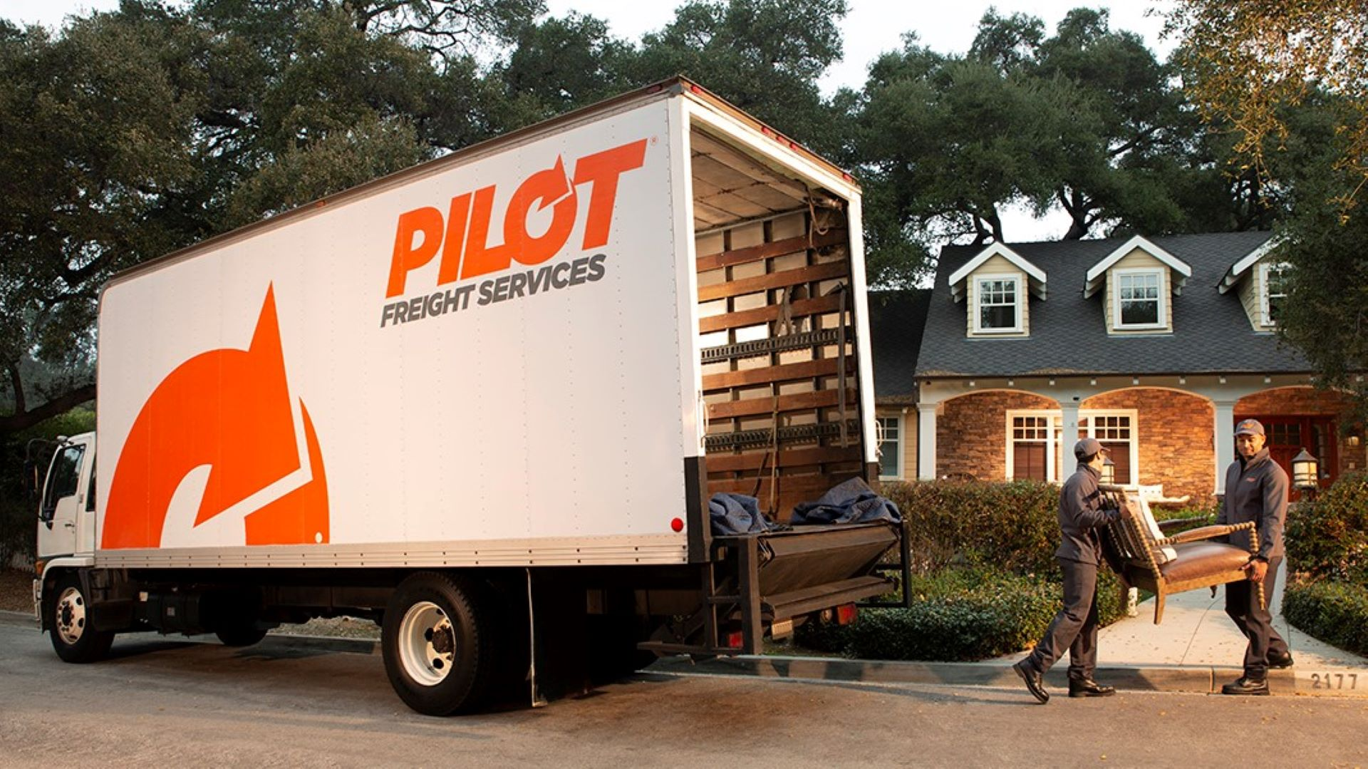 Drivers unload furniture from a truck to bring in a home. Pilot Freight is the company.