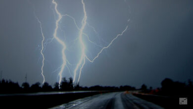Lightning across the sky with a tractor-trailer in the distance.