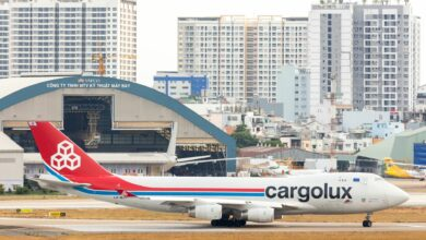 A Cargolux jumbo jet taxing at airport with Ho Chi Minh City apartments in background.