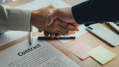 A handshake over a contract lying on table.