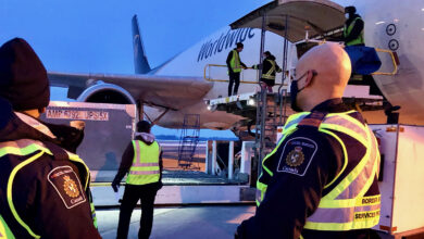 Canada Border Services Agency officers look on as cargo is unloaded from a UPS cargo flight.