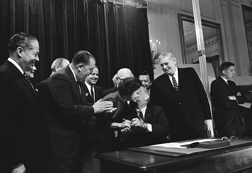 President Johnson kisses Lady Bird Johnson after signing the Highway Beautification Act of 1965. To her left (leaning in clapping) is U.S. Sen. Jennings Randolph, the bill's primary Senate sponsor. (Photo: LBJ Library)