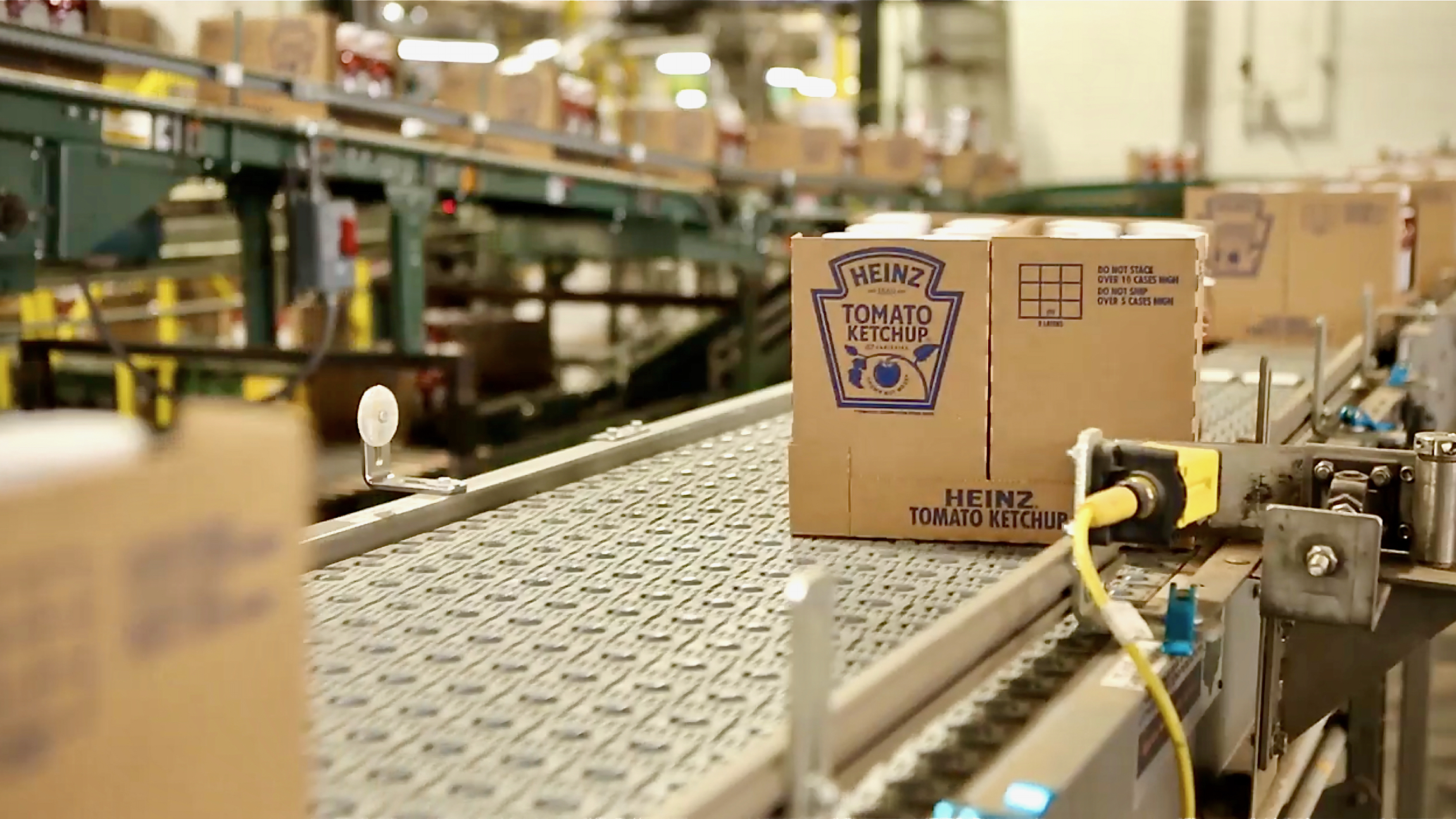 A cardboard box of Heinz ketchup moves on a conveyer belt, illustrating an article about Kraft Heinz.