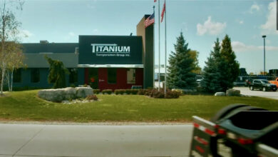 The outside of a Titanium Transportation Group office with a US and Canadian flag flying in front of it.