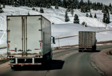 Trucks on the highway seen from behind in the Denver area with snow and trees in the background.