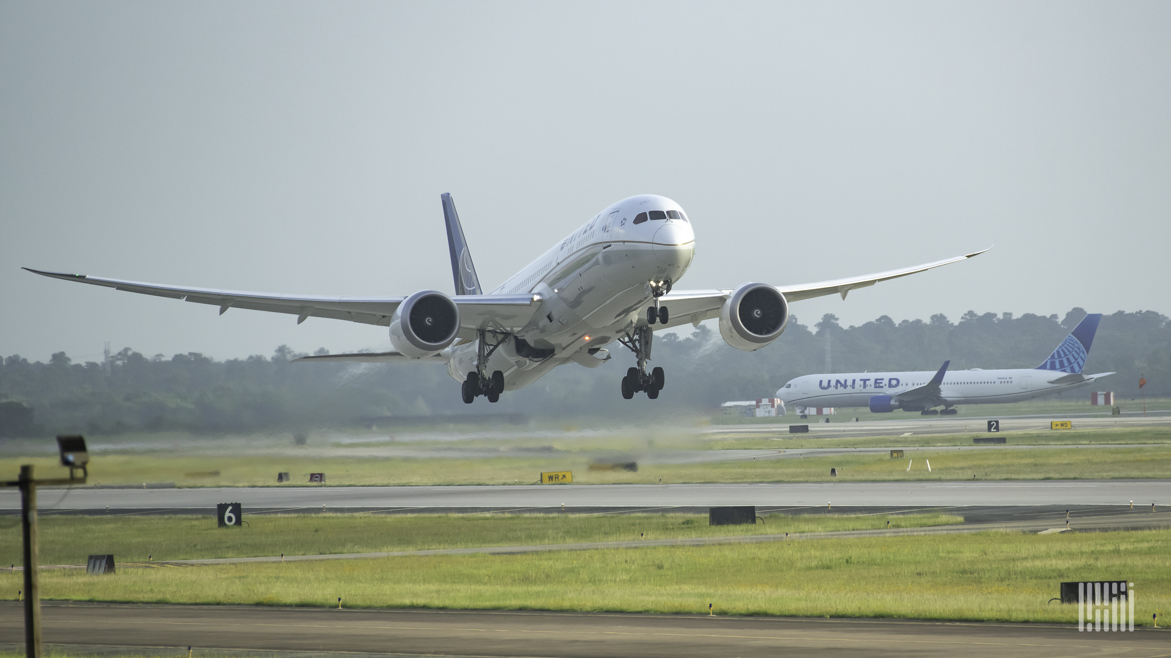 Front view of a plane taking off, with a United Airlines plane in the background.