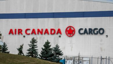 Air Canada Cargo lettering on side of building with some pine trees in foreground.