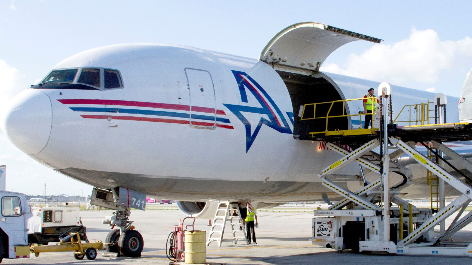 A white jet with cargo door wide open on a bright sunny day.
