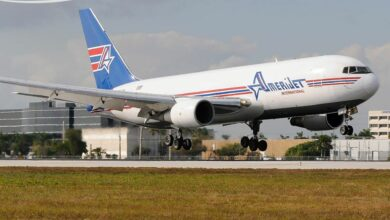 A white Amerijet cargo plane with a blue tail landing on runway.