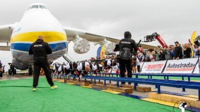A group of men crawling to pull a massive plane with crowed cheering on.