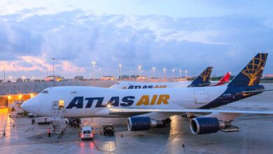 Atlas Air jumbo jets with blue and gold lettering sit on tarmac at dawn.