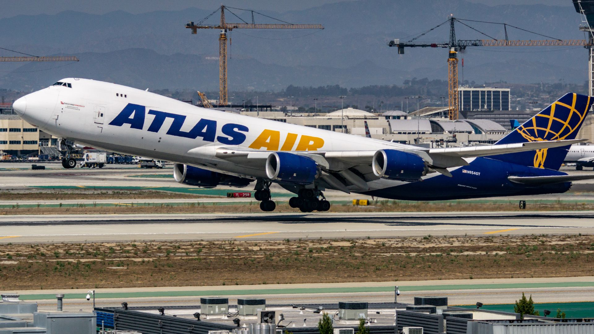 An Atlas Air jumbo cargo jet takes off, with front wheel in air. The plane is white, with purple and gold lettering.