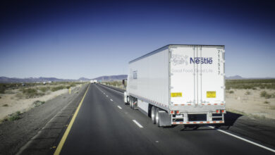 A photograph of a truck traveling down a highway in the desert.