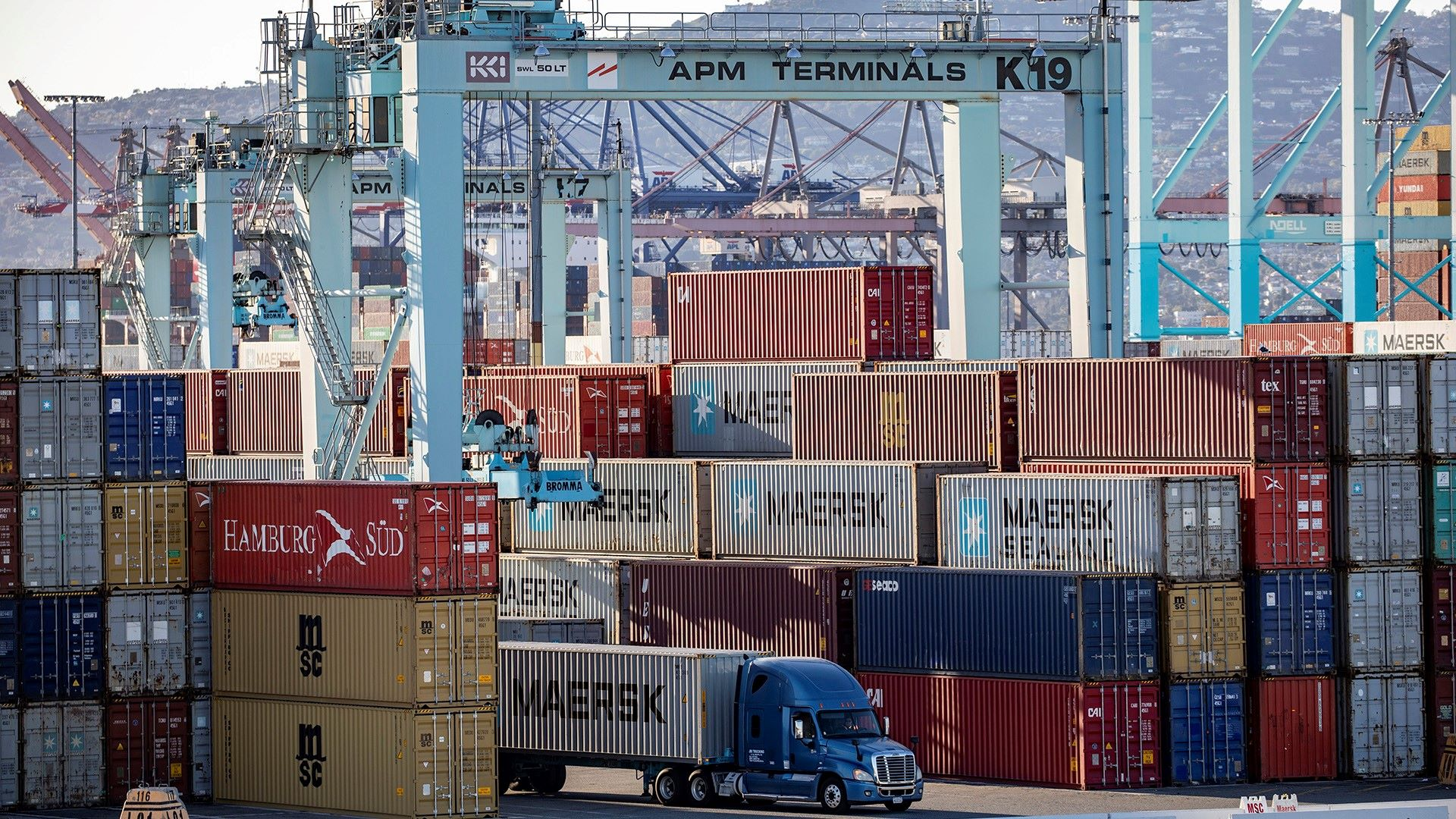 A truck driving through large stacks of containers at a port.