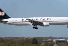 A Cargojet jet, white with blue tail, comes in for a landing with wheels extended.