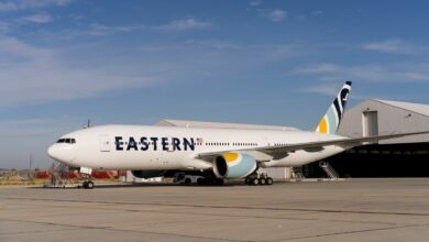 An Eastern Airlines jet on tarmac in front of a hangar building.