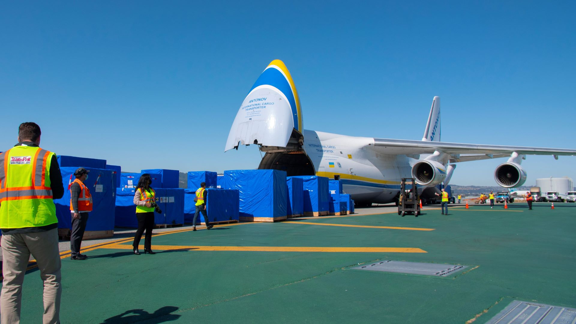 Large crates covered with blue tarps lined up in front of a nose-loading air cargo jet on a clear blue day.