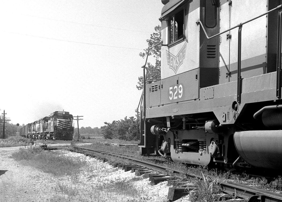 A Gulf, Mobile & Ohio locomotive has taken the siding with its freight at Bemis, Tennessee as a counterpart passes during June 1966. (Photo: Bill McCoy/Warren Calloway Collection/American-Rails.com).