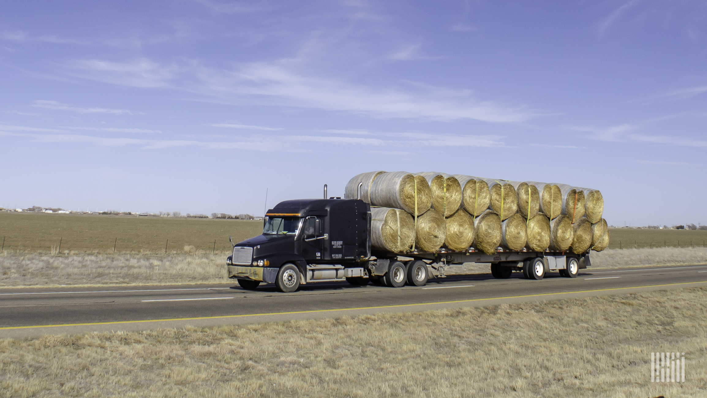 Flatbed truck carrying large bales of hay.