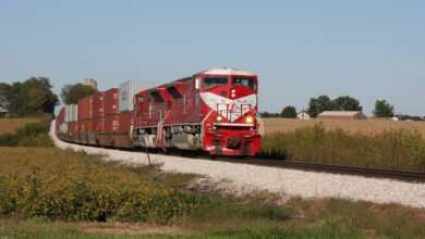 A photograph of a train rolling through a grassy field.