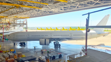A large white jet is moved through the door of a large airplane hangar.
