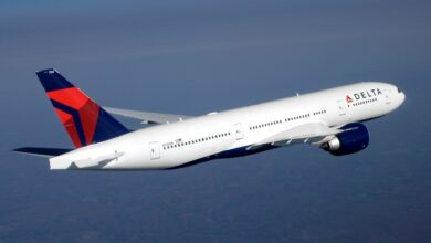 A Delta Air Lines jet with white body and blue/red tail in flight, as viewed from side rear.