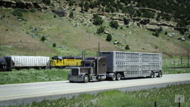 A photograph of a truck on a highway and a train in the background.