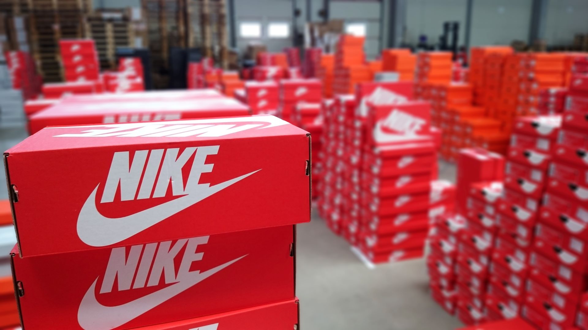 Stacks of red Nike shoe boxes in a warehouse.