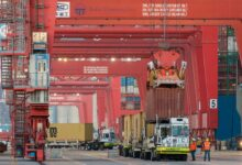 Giant cranes maneuver containers onto yard dollies on the dock.