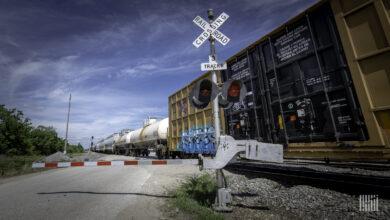 A photograph of a train at a rail crossing.