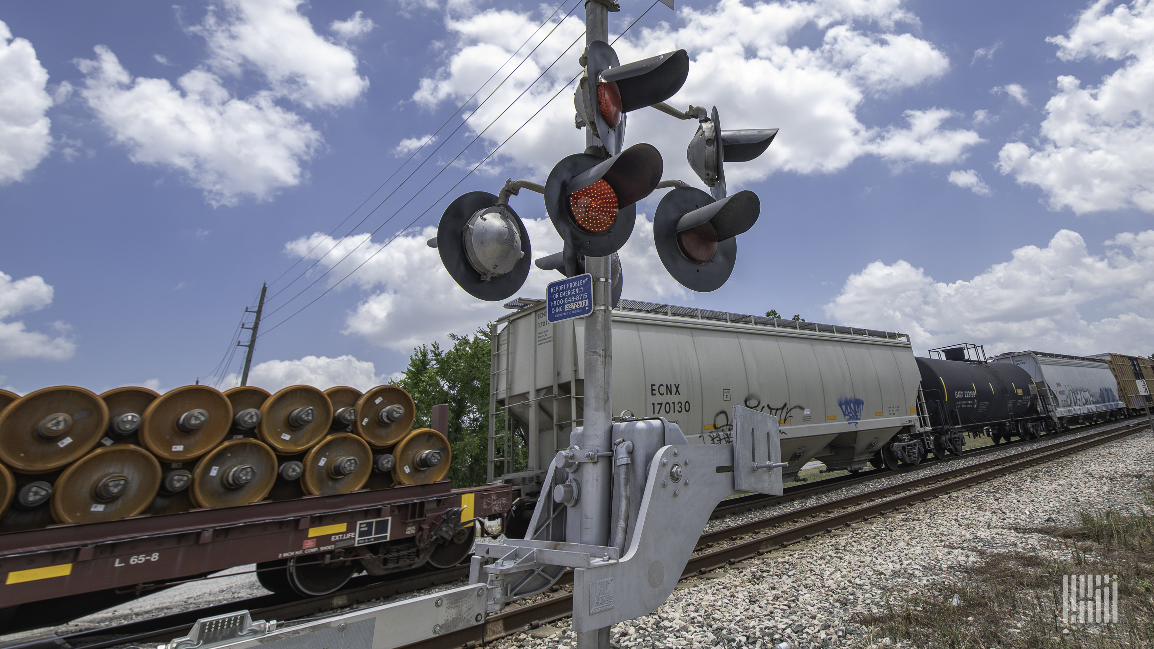 A photograph of a train passing by a rail crossing on a sunny day.