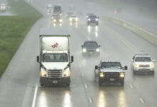 Trucks and cars on a highway during heavy rain.