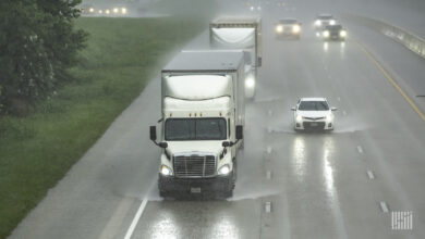 Tractor-trailers on a highway in heavy rain.