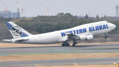 A white jumbo jet with blue lettering takes off with nose lifted in air.