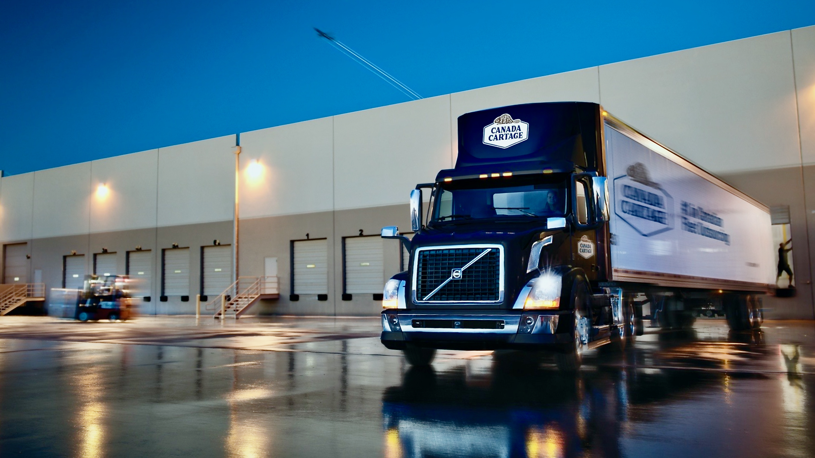A truck from Canada Cartage exits a loading dock.