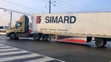 A tractor-trailer logo SIMARD makes a turn on a street to illustrate an article about the Canadian election.