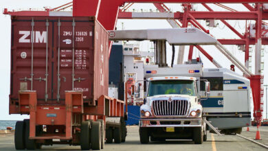 Canada Border Service Agency officers inside a truck prepare to inspect a container at a port facility.