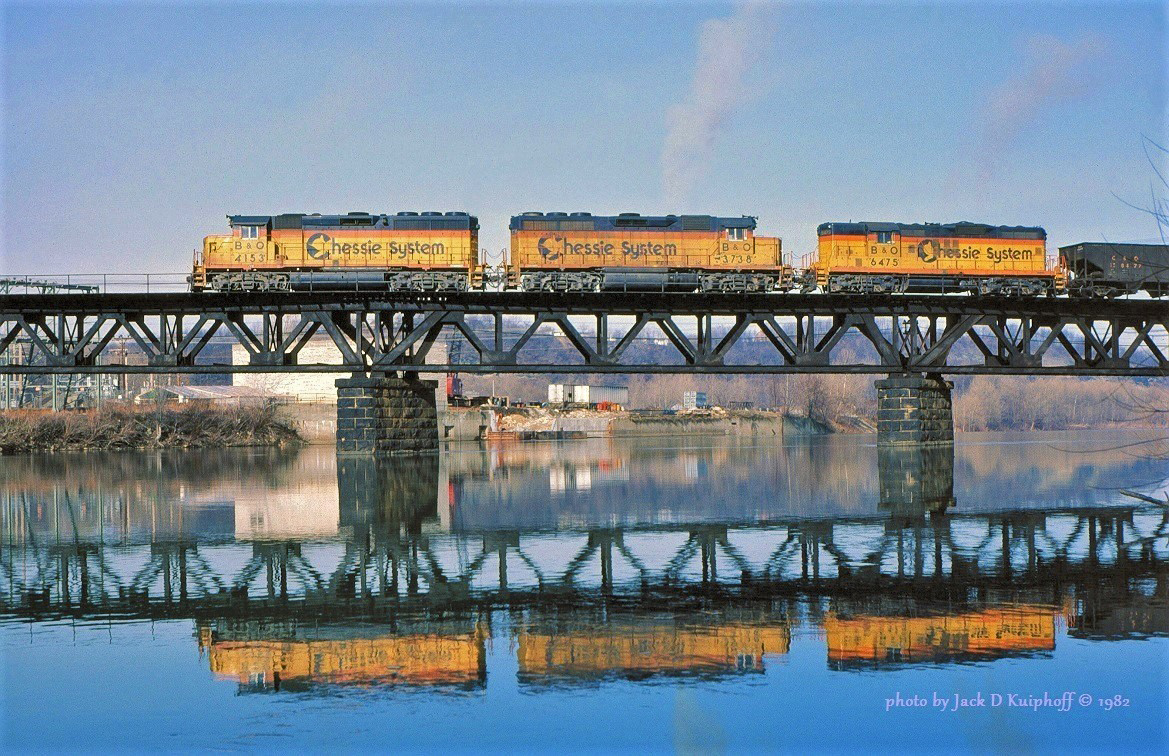 """Chessie System/Baltimore & Ohio locomotives cross the Youghiogheny River at South Connellsville, Pennsylvania and head down the B&O's """"Sheep Skin"""" line to Fairmont, West Virginia with an empty hopper train on January 1, 1982. (Photo: Jack Kuiphoff/American-Rails.com)"""