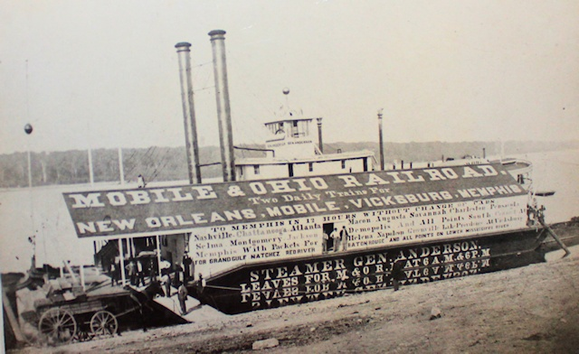 """A unique """"billboard"""" for the Mobile & Ohio Railroad on the roof and side of the port facilities in Columbus, Kentucky. Note the paddlewheeler behind the facility on the Mississippi River. (Photo: CBSP/Columbus, Kentucky)"""