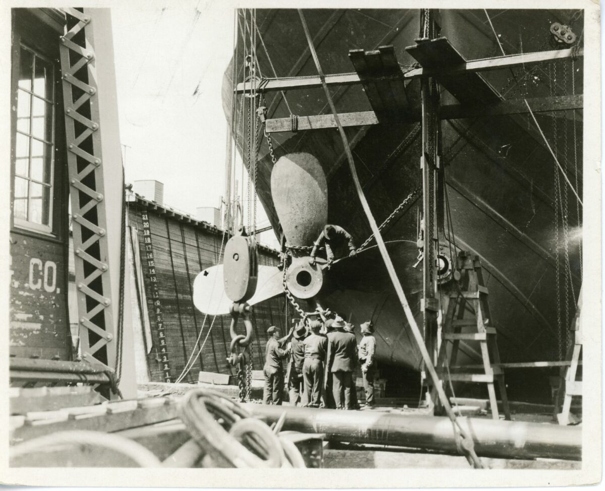 Workers surround the shaft and propeller of a ship under construction at the Ira S. Bushey & Sons Shipyard. (Photo: South Street Seaport Museum)